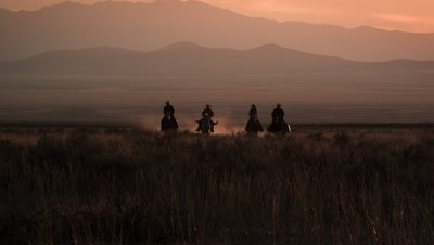 Slow motion shot of cowboys galloping in distance.