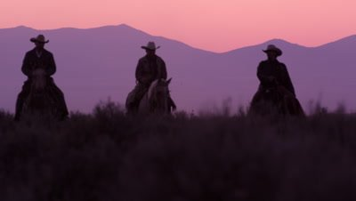 Slow motion shot of cowboys riding towards the camera with pink sky in the background.