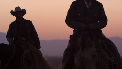 Close up shot of cowboys and horses in the sunset. Slow motion