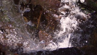 Shot from top of waterfall as it falls downward. Slow motion.