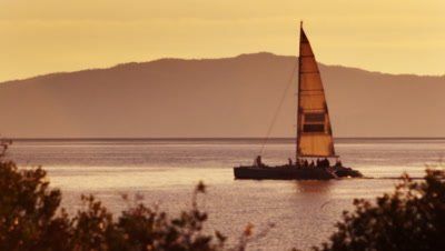 Static shot of sailboat on water with orange sky. Shot at Emerald Bay State Park, Lake Tahoe, CA.