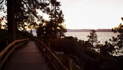 Static shot of a man walking on a path at sunset at Sand Harbor State Park on Lake Tahoe.