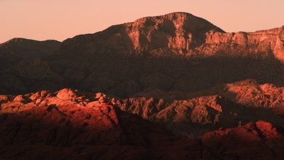 Distant shot of night falling over red mountains