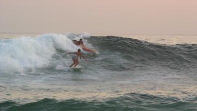 Slow motion, pan shot of surfer riding wave