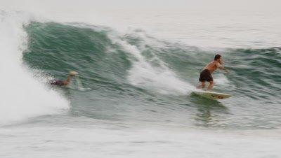 Close daylight shot of surfer riding a wave off the coast of Rio de Janeiro, Brazil.