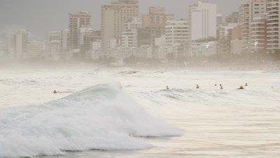 Camera follows surfer riding a wave into Leblon's shoreline