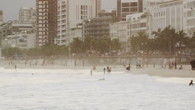 Slow motion, pan shot of beach goers, waves, and buildings in Leblon.