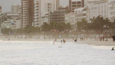 Slow motion, pan shot of beach goers, waves, and buildings in Leblon.