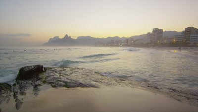 Static shot of surfers, beach goers, and landscape at sunset on Ipanema Beach.