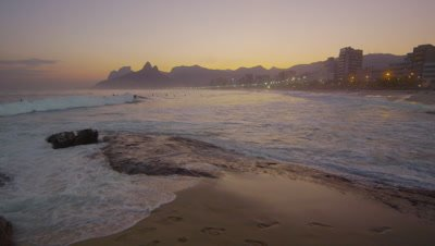 Slow motion shot of waves hitting Ipanema beach at sunset