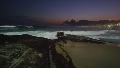 Slow motion tracking shot of the ocean flowing in against the Arpoador Rocks