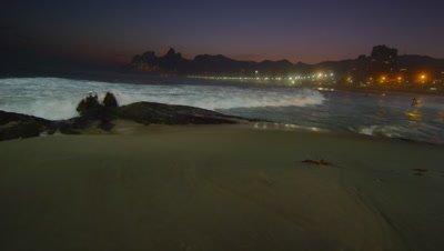 Slow motion, pan left of the waves flowing in at Ipanema beach