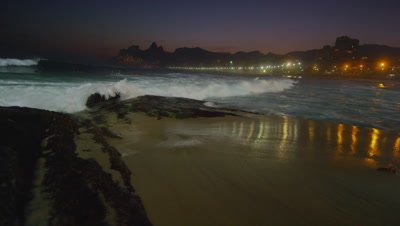 Slow motion, pan right of waves crashing against Ipanema beach at night