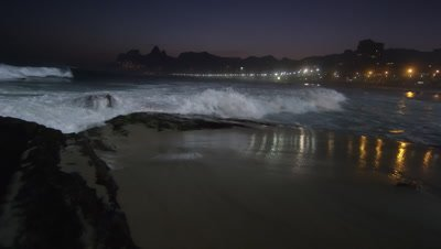 Slow motion, pan right as the tide flows up on Ipanema beach at night