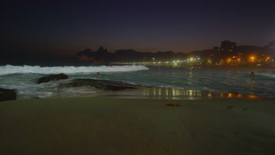 Slow motion, pan left of a night surf on Ipanema beach in Rio De Janeiro