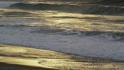 Tilting shot of waves breaking on Ipanema beach at sunset