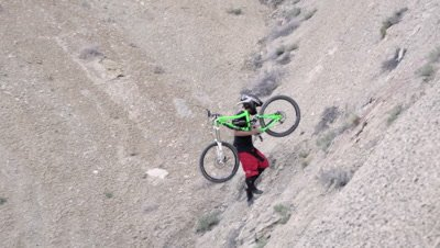 Slow motion of 2 guys carrying mountain bike up a steep hill.
