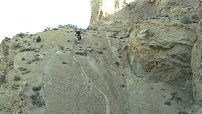 Slow motion of guy riding mountain bike down steep dirt hill.