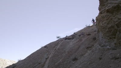 Slow motion of guy riding mountain bike down steep dirt hill.Slow motion of guy riding mountain bike down steep dirt hill.