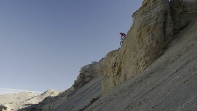 Slow motion of guy riding mountain bike off rocky cliff down a steep rocky slope.