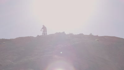 Slow motion of guy riding mountain bike and skidding down hill.