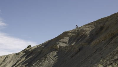 Slow motion of guy riding mountain bike on horizon of dirt hill.