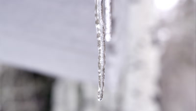 Icicles melting from roof of small building.