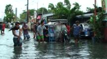 People Push Broken Motorbike Through Flooded City Street