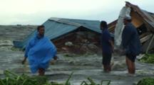 People Walk Through Flood Waters Near Destroyed Slum