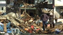 Japan Tsunami Aftermath - Survivors Walk Through Wreckage In Kesennuma City