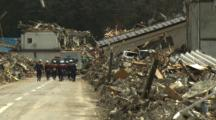 Japan Tsunami Aftermath - Rescuers Walk Through Destroyed Streets Of Rikuzentakata City