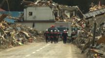 Japan Tsunami Aftermath - Rescuers Walk Through Destroyed Streets Of Rikuzentakata City