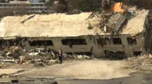 Japan Tsunami Aftermath - Woman Runs From Destroyed Building In Onagawa City