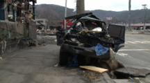 Japan Tsunami Aftermath - Crushed Car Lies On Street In Ishinomaki City