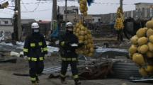 Japan Tsunami Aftermath - Fire Crew Walks Through Destroyed Port In Ishinomaki City