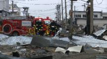 Japan Tsunami Aftermath - Fire Crew Walks Through Port In Ishinomaki City