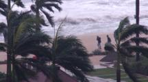 Men Walk Along Beach In Strong Winds With Rough Seas