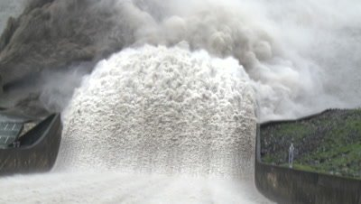 Flood Waters Flow Down Dam Spillway At Hydroelectric Plant