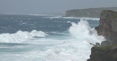 Rough Sea And Large Waves Crash Into Rugged Coastline