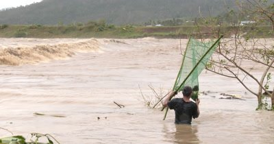 Fisherman Wades In Flooded River After Hurricane