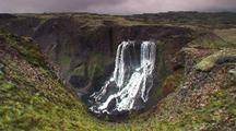 Icelandic Waterfall Cascades Down Cliff Into Valley