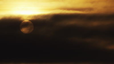 Sunrise scenic of sun rising through heavy clouds.  Med.