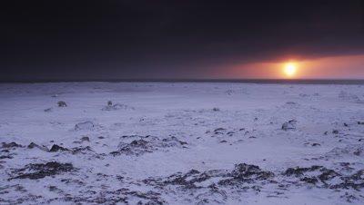 Sunrise scenic.  Two polar bears mill around in bizarre, barren ice field with a brilliant sun rising over the horizon under heavy clouds.  Wide.