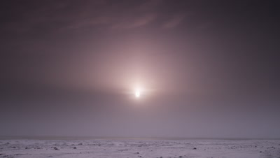 Scenic.  Sun shines through a hazy cloud bank across an icy, rocky wasteland.  Extreme Wide.