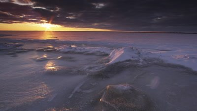 Timelapse of sun setting over snowy frozen lake.  Wide.
