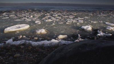 Pan across half frozen bay at sunrise, ending on frozen chunk of ice stranded on boulder.  Wide.