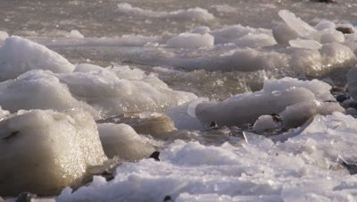 Chunks of ice rock against a shoreline as waves break on partially frozen sea.  Med.
