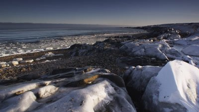 Partially frozen bay at sunrise.  Ice coated boulders with chunks of ice floating in breaking waves.  Wide.
