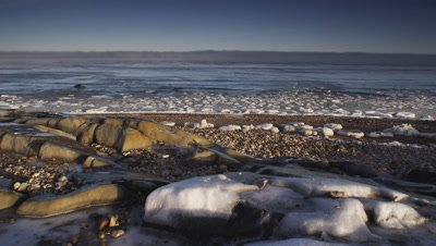 Pan across partially frozen bay at sunrise.  Ice coated boulders with chunks of ice floating in breaking waves.  Wide.