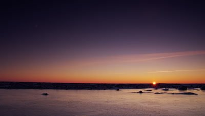 Scenic - Sun sets on horizon  over a bare, glassy sheet of ice and under a deep blue sky.  Wide.
